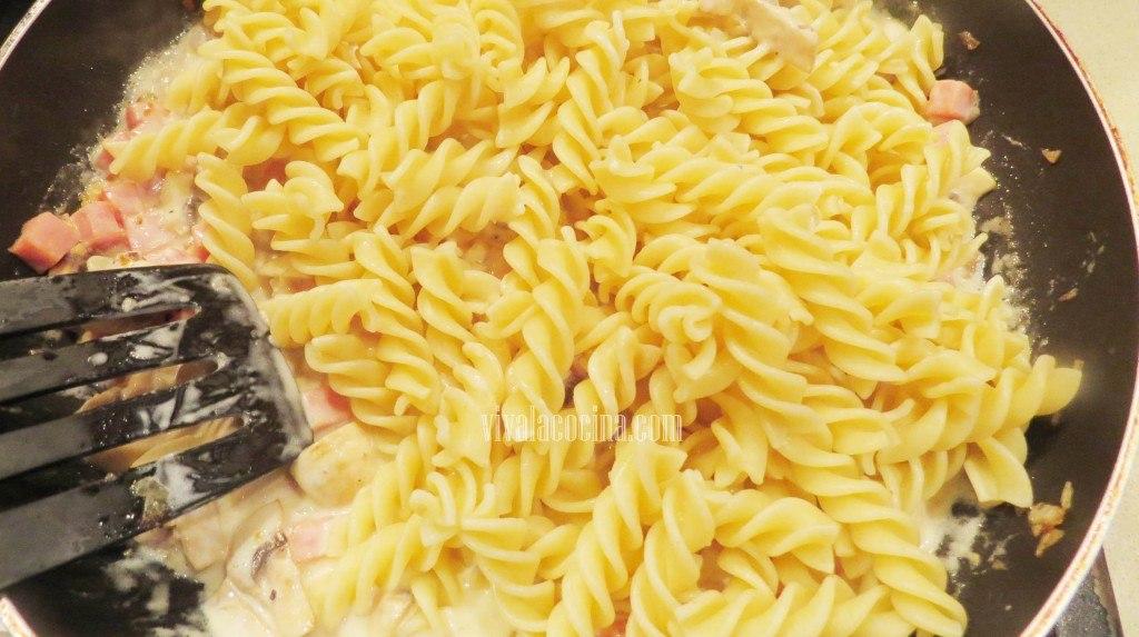 Añadir la Pasta a la salsa para hacer Fusilli a la crema con Champiñones