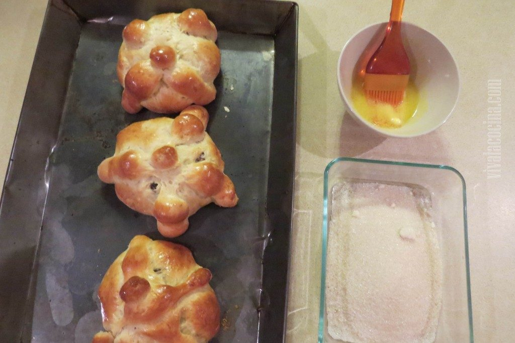 Barnizar con Mantequilla los panes de Muerto salidos del horno