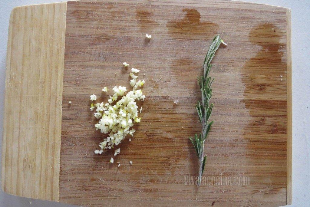 Picar el Ajo, cebolla y romero para la receta de lomo de cerdo