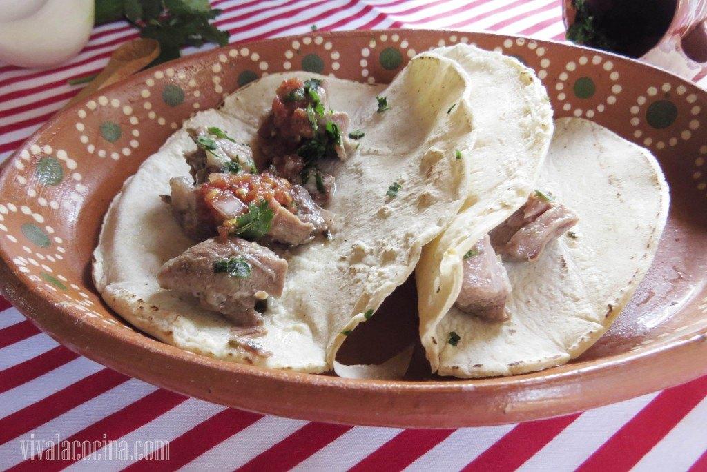 Servir la carne de chambarete en tacos con tortilla de maíz y acompañarlos con la salsa roja.