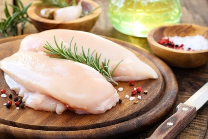 Raw uncooked chicken breast with fresh rosemary sprig and pink pepper corns and kosher salt on rustic wooden cutting board