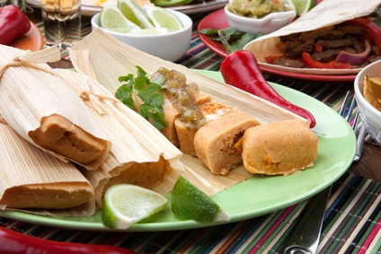 Assorted Mexican dishes, with chicken tamales with green salsa as the main subject.