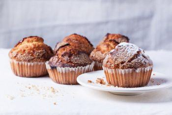 Homemade muffins with brown sugar over white textile