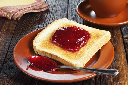 Toasted bread with jam in plate on dark wooden table