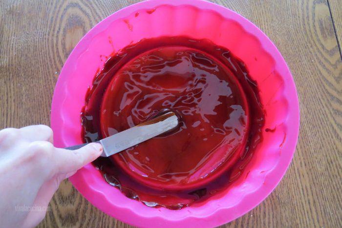 Untar caramelo líquido en el molde para hacer el budín de pan con manzanas