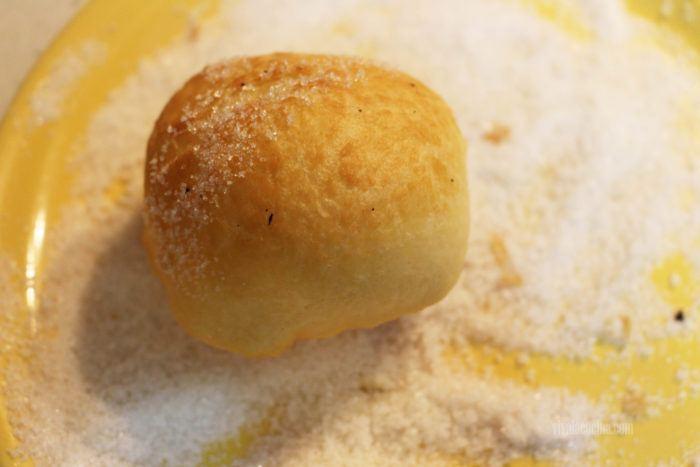 pasar por azúcar los sapitos dulces recién fritos