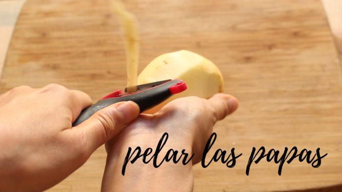 pelar las patatas para hacer tamales de verduras